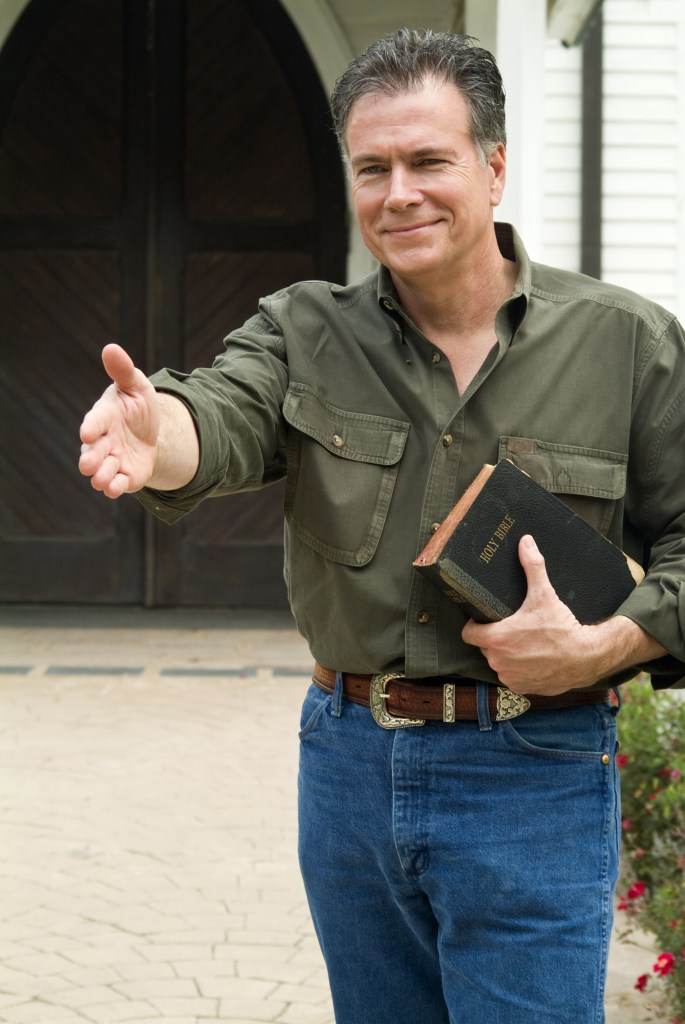 A smiling man standing in front of a church, holding a bible, with his hand extended in a welcoming gesture.