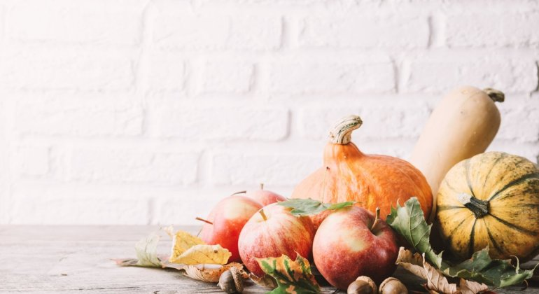Fruta y calabazas sobre mesa de madera