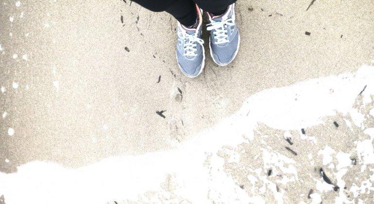 Pies de mujer a la orilla del mar