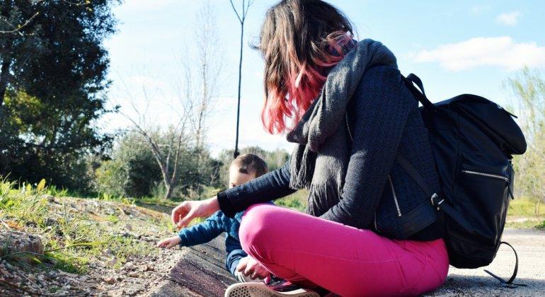 La suerte de ser madre a tiempo completo, mamá sentada en el parque jugando con un bebé