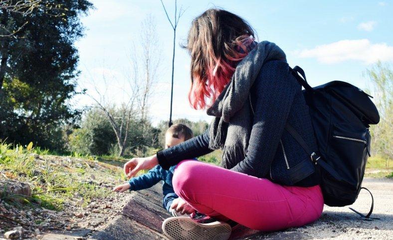 La suerte de ser madre a tiempo completo, mamá sentada en el parque jugando con un bebé de un año