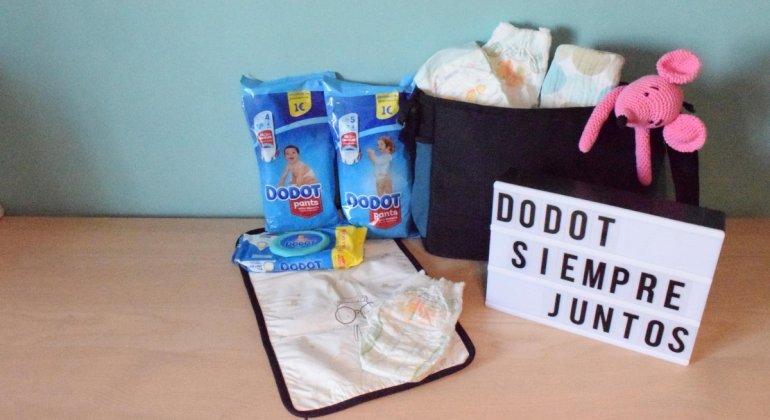 Foto con cambiador lleno de pañales dodot junto con toallitas, un bolso de carrito, un peluche de ratón rosa y un cartel tipo cine con la frase Dodot siempre juntos