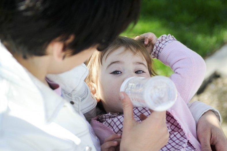 Madre dando biberón a su hija, la lactancia artificial está mal vista
