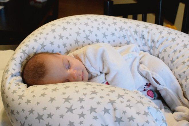 Hija duerme sobre el cojín de lactancia