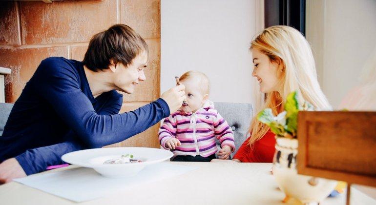 Un padre dando de comer a su bebé en un restaurante al lado de su pareja, para carta abierta a los padres del niño que chillaba en el foster's hollywood