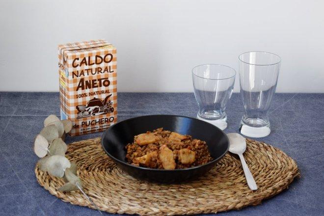 Portada para receta tradicional de lentejas con Caldo aneto de puchero, lentejas con brick de caldo, vasos de cristal y rama de eucalipto sobre mantelito de rafia
