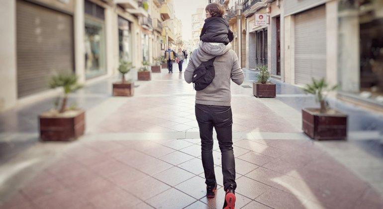 Foto de padre con hija en los hombros caminando casi solos, la conciliación no existe son los padres