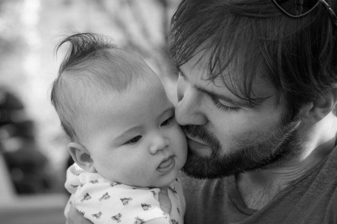 Padre besando a su bebe, la conciliación no existe son los padres