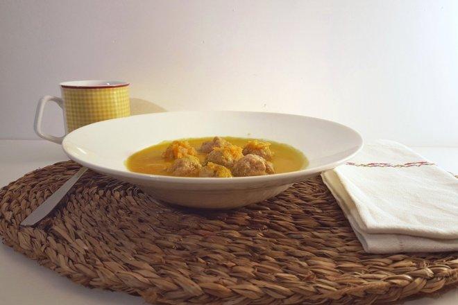 Vista detalle de un plato de groentensoep met balletjes, sopa de verduras con albondigas, con una taza de aneto y una servilleta con bordados en los tonos de la bandera holandesa