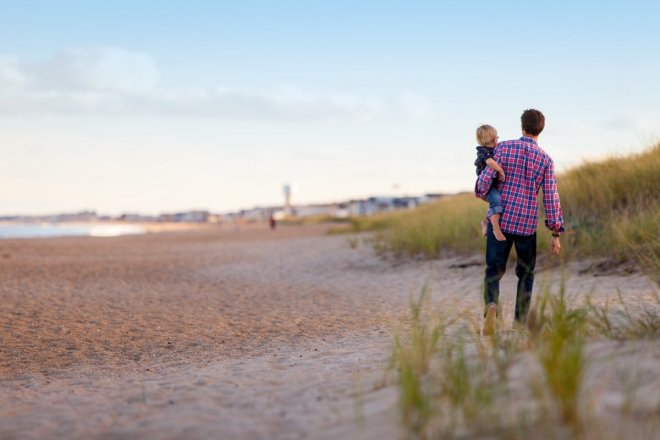 Padre paseando con hijo por la playa, el papel del padre en la lactancia materna como agente facilitador.