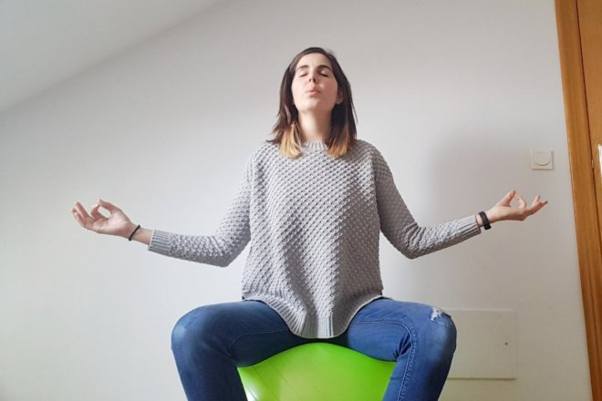 Mujer meditando encima de una pelota de pilates, como preparación al parto