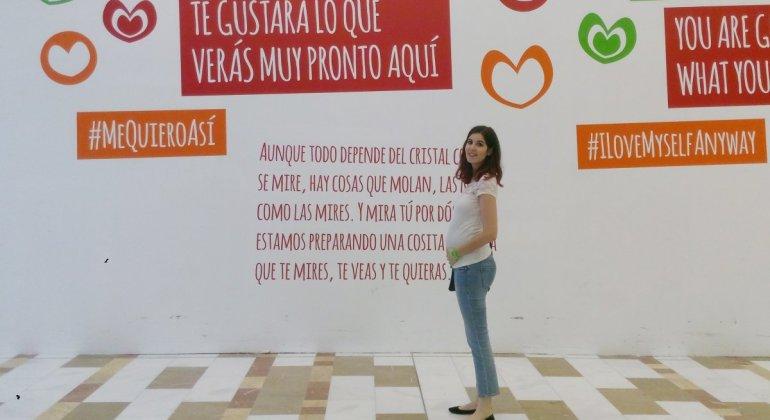 Chica embarazada delante de un cartel motivador, preparación al parto