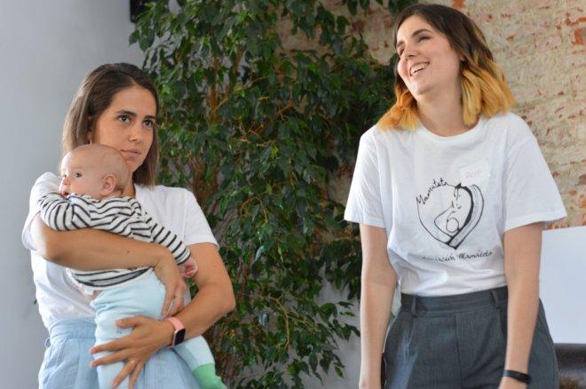 Madres en la I jornada de lactancia materna de Edulacta, una sujetando a su bebé y la otra riendo.