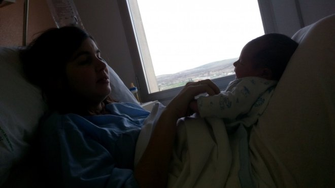 Mujer que ha dado a luz hace horas, con su bebé y un biberón pirata, postparto inmediato, después de parir quiero existir.