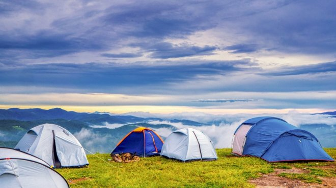 Tiendas de campaña en paisaje montañoso, como broma de madres que dan el pecho sin enseñar la teta escondidas tras un cobertor de lactancia.