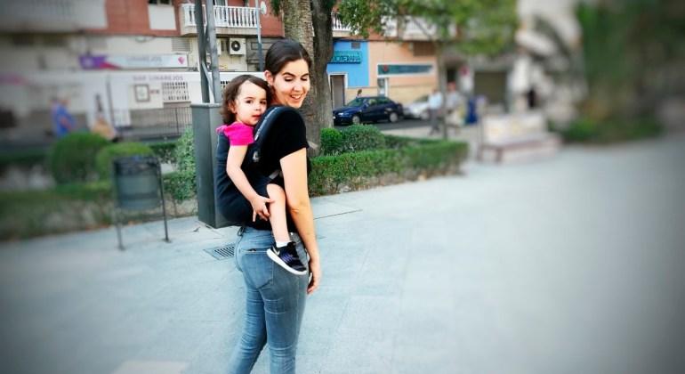 Mamá porteando a su niña de 2 años a la espalda con la mochila de porteo toddler más barata del mercado, la Ling Ling d'amour P4 Preschool