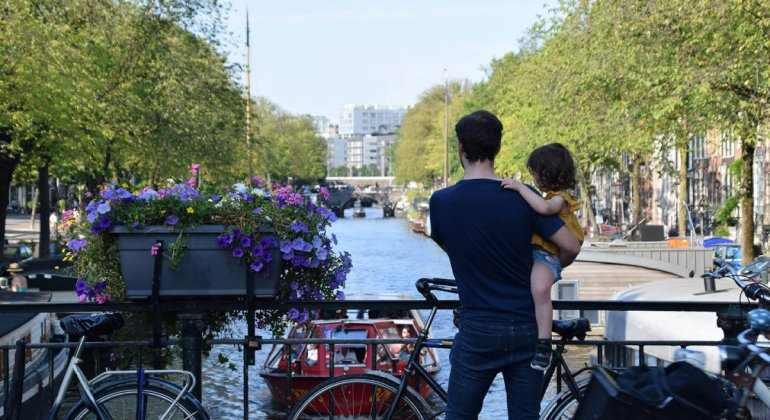 padres sosteniendo a su hija en un canal de Amsterdam durante una visita de 2 dias