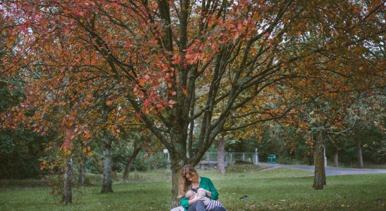 Mujer dando el pecho en el parque, es necesario visibilizar más la lactancia materna