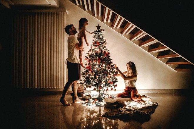 Famiilia decorando el árbol de Navidad para la llegada de Papa Noel y los Reyes Magos