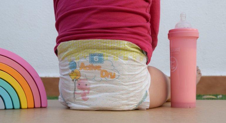Niña sentada junto a un arcoiris y un biberón llevando pañales de la marca Nunex