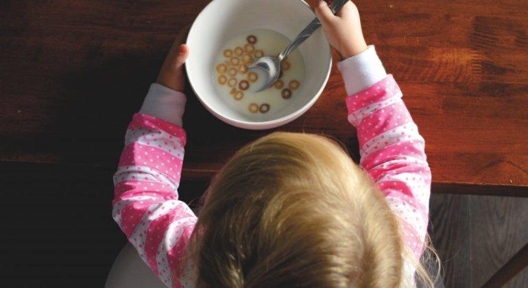 pautas a la hora de empezar la alimentación complementaria, para que los niños coman solos como la niña de la foto, comiendo un bowl de cereales.