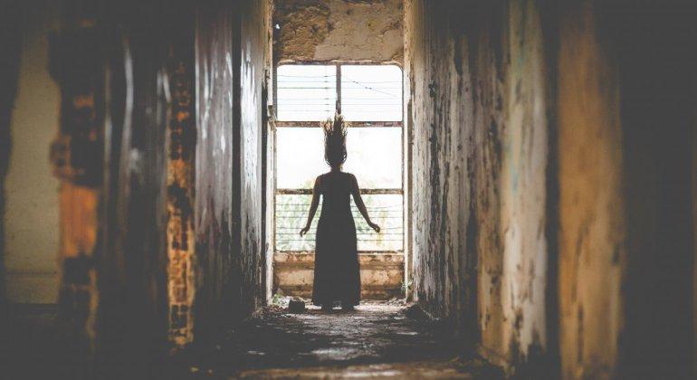 Postparto y otras historias de terror, mujer delante de ventana en entorno terrorífico