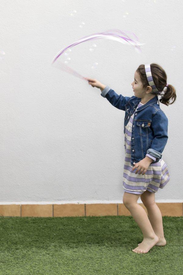 Niña con vestido lila y beige de punto de algodón reversible de la marca Giro, jugando con burbujas y cintas.