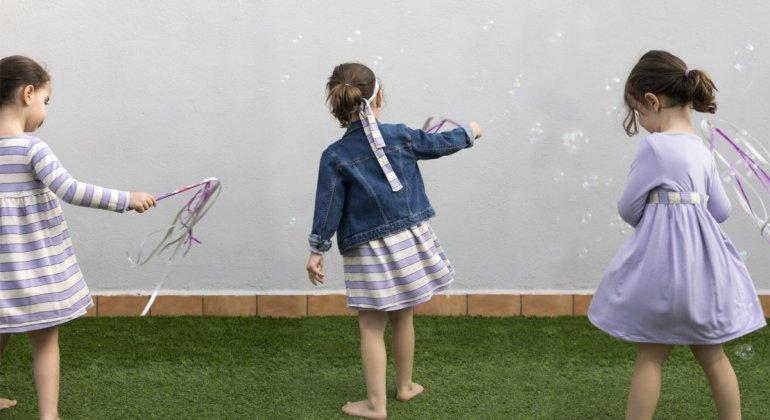 Foto de niña en 3 poses con el mismo vestido reversible de la marca Giro usado de diferentes maneras