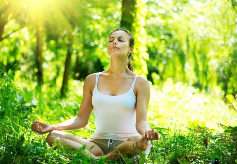 Mujer meditando con las piernas cruzadas en una mala postura de meditación.