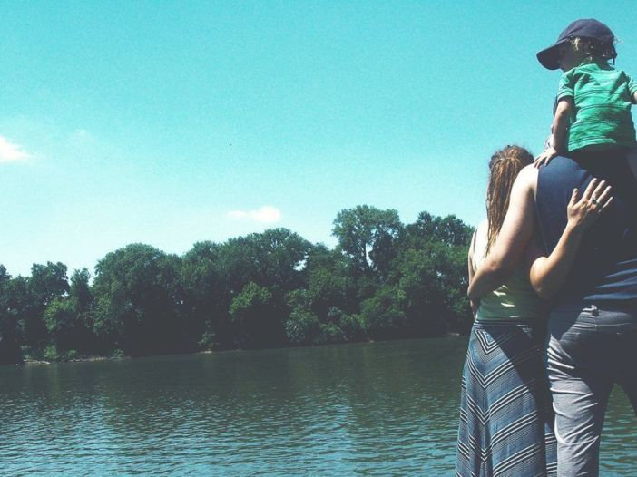 Fotografía de familia disfrutando de tiempo de calidad junto a un lago