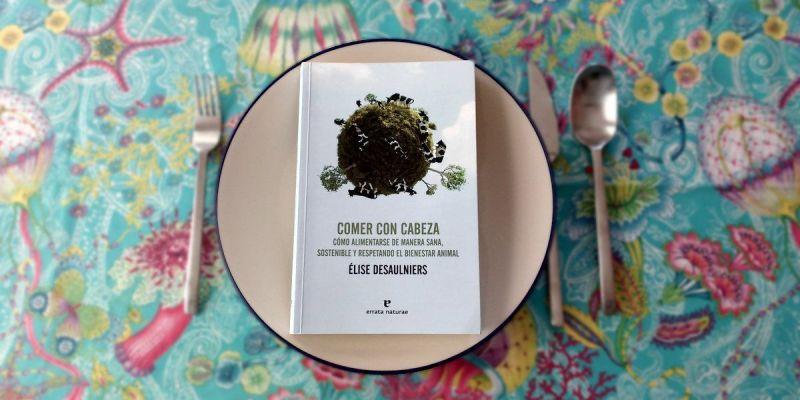 Fotografía del libro Comer con cabeza. Cómo alimentarse de manera sana, sostenible y respetando el bienestar animal publicado por Errata Naturae colocado sobre un plato