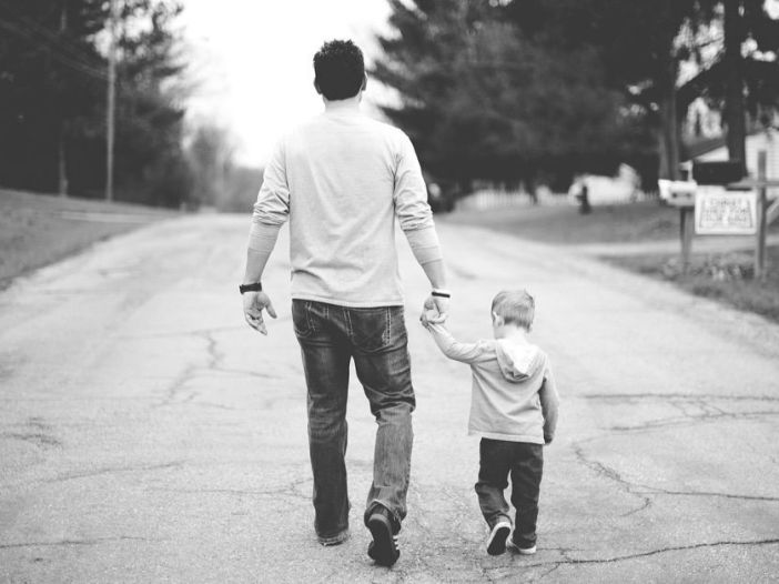 Fotografía de un hombre paseando con un niño pequeño