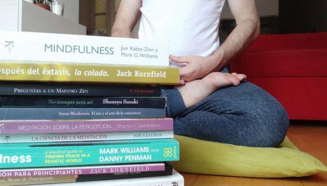 Fotografía de Iñaki Calvo meditando con una pila de libros sobre mindfulness y meditación delante