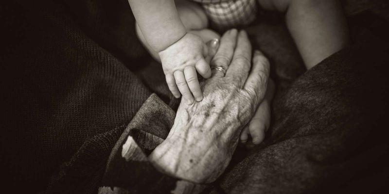 Fotografía de la mano de una anciana tocando la mano y el pie de un bebé. Rod Long (Unsplash).