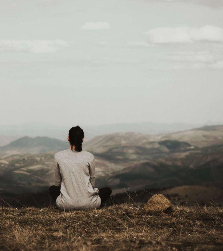 Mujer meditando. Fotografía en una montaña. Obra de Milan Popovic on Unsplash