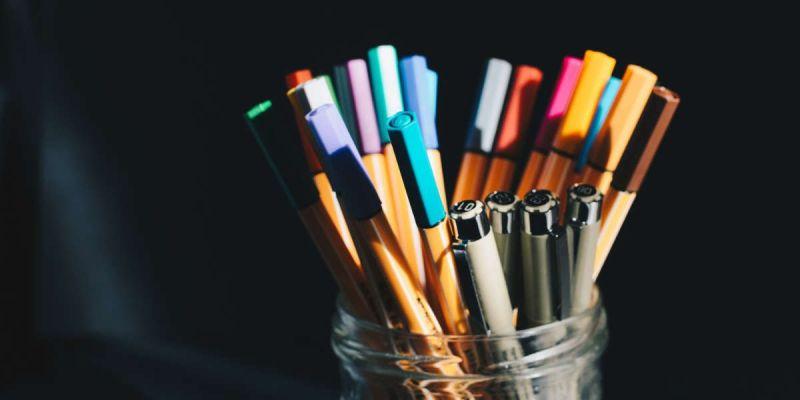 Fotografía de bote de cristal con rotuladores de colores