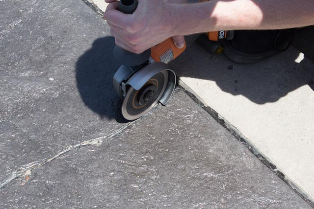 Cleaning out a crack with a grinder in a stamped concrete driveway for MatchCrete Clear repair.