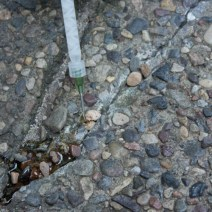 Exposed aggregate concrete crack repair with Roadware MatchCrete Clear and needle tip cartridge applicator.