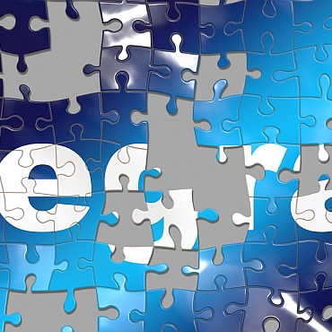 Jigsaw puzzle in blues with pieces missing. Section of letters that spell integration.