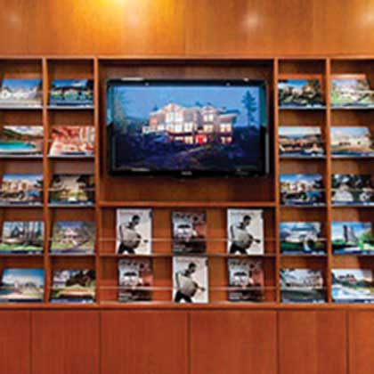Wall unit with TV and Sotheby's Marketing brochures and flyers.