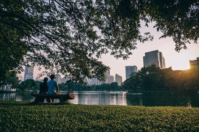 Man and woman viewing city from park bench