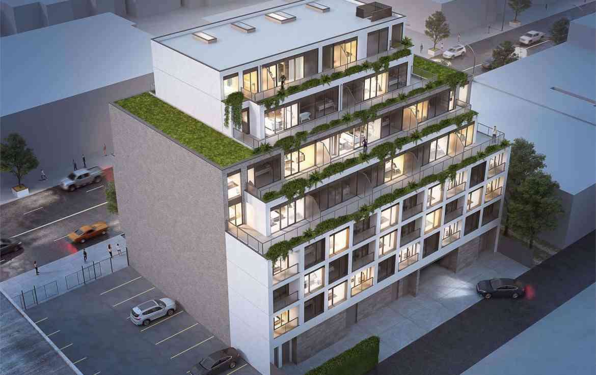 Rendering of THEO Condos Danforth Toronto exterior from birds-eye-view at night.