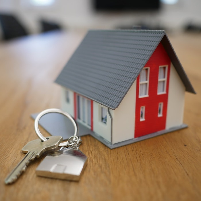 Tiny model of a red and white house next to a set of keys.