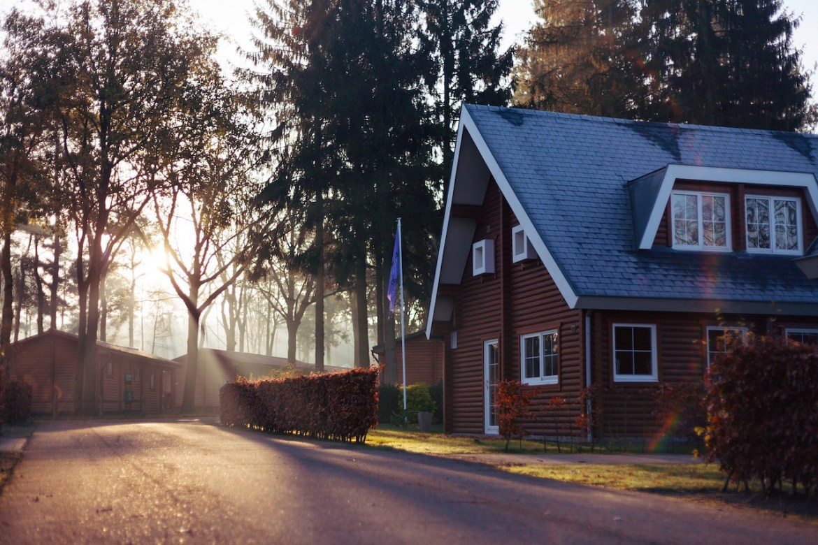 Beautiful country home with light coming through nearby trees.