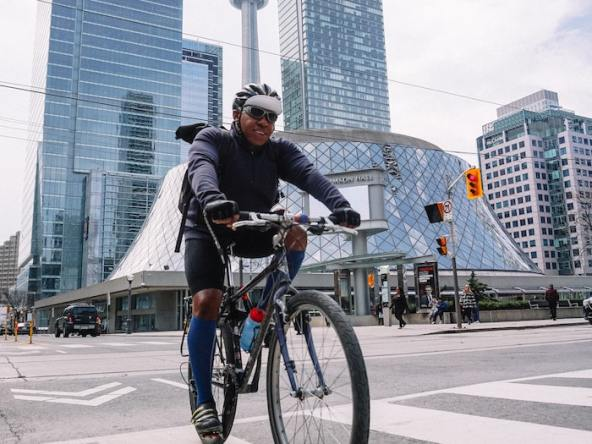 Man biking near the Roy Thomson Hall, Simcoe Street, Toronto, Toronto, ON, Canada with CN Tower in the background.