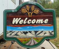 wood welcome sign hand crafted and artist painted for house in Central Butte Sask. sandblasted cedar signs for any need by Condor signs Vernon BC.