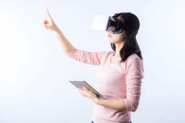 Usuária da realidade virtual em demonstração com o uso do óculos e do seu tablet