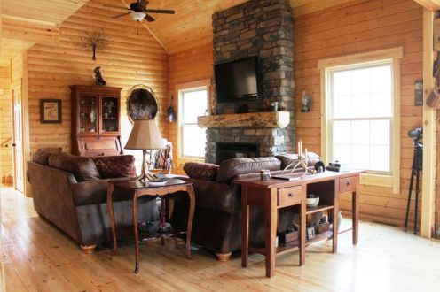log home great room with stone fireplace