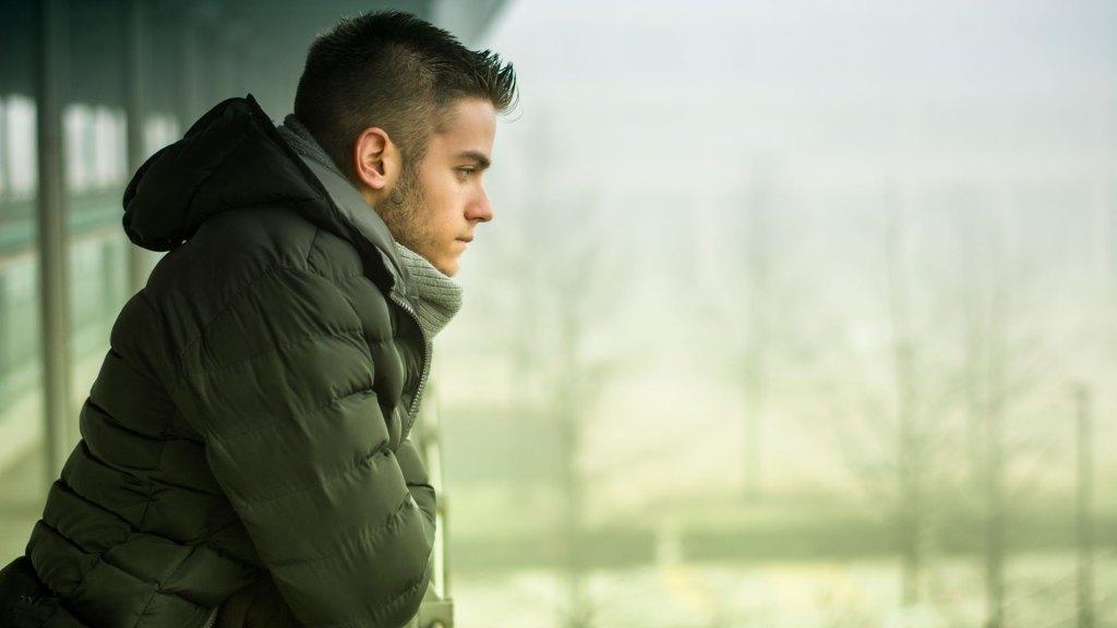 sad boy leaning over rail