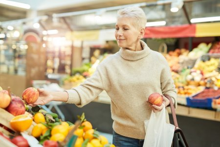 older female grocery shopping for fruits